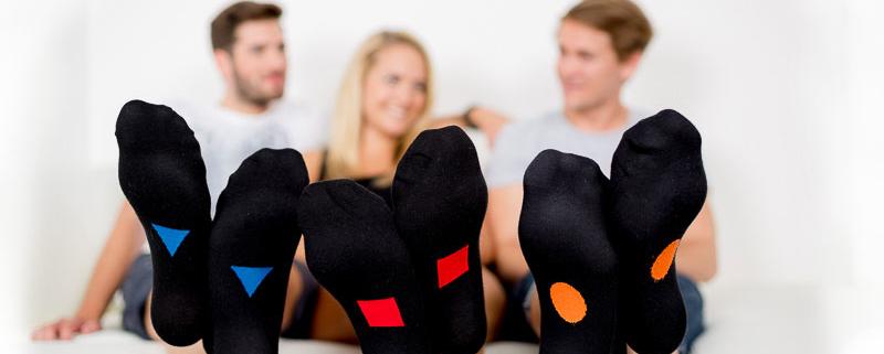 drei Personen mit hochgelagerten Füßen in Symbolsocks